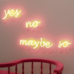 scritta la neon su un muro: yes, no, maybe so.